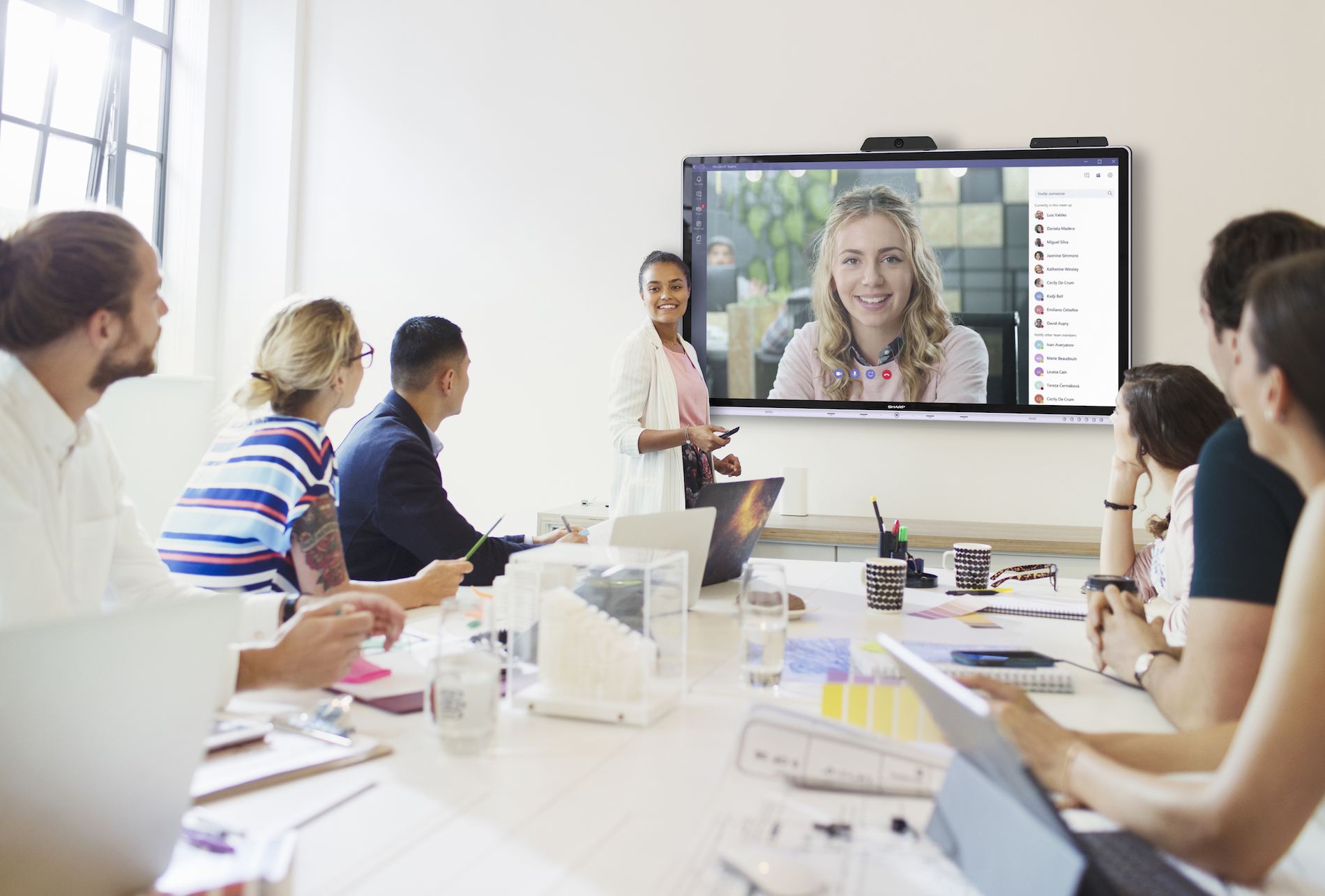Confident businesswoman at television screen leading conference room meeting